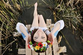 stock photo of wet feet  - girl in a flower wreath on his head sitting on the bridge and wets feet in the river - JPG