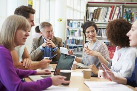 picture of mature adult  - Group Of Mature Students Collaborating On Project In Library - JPG