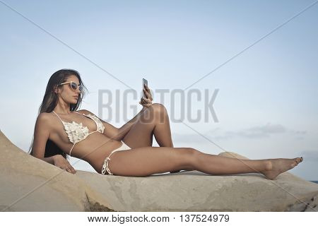 Fashionable woman in swimsuit doing a selfie