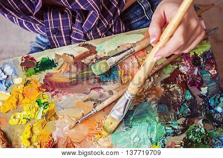 Brush And Oil Paints On A Palette, Paint A Picture Of The Artist\'s Hands, Texture Mix Paint In Diffe