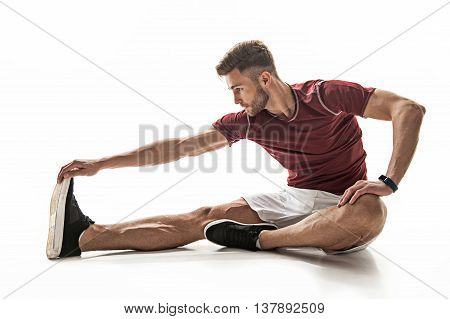 poster of Fit young man is doing exercise with concentration. He is stretching hand to foot while sitting on floor. Isolated
