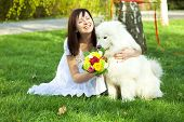 picture of laika  - Bride with dog Samoyed sitting on the grass - JPG