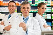 Pharmacist with his team standing in pharmacy or drugstore in front of shelves with pharmaceuticals