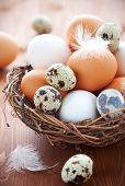 stock photo of easter basket eggs  - Different types of eggs in a  nest with feathers on a wooden table - JPG