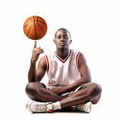 Постер, плакат: Молодой африканских человек держащий в баскетбол на пальце