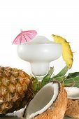 picture of pina-colada  - A pinacolada with umbrella surrounded by pineapple and coconut - JPG