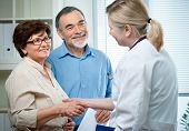 stock photo of medical exam  - senior couple visiting a doctor at the doctor - JPG