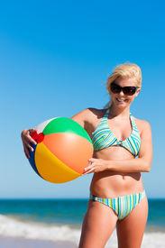 pic of beach-ball  - Attractive Woman in bikini standing in the sun on beach under a blue sky  - JPG