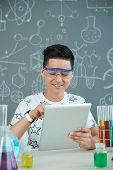 Smiling Teenage Pupil Wearing Safety Goggles Sitting At Desk Of Chemistry Classroom And Taking Neces poster