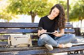 Attractive Young Caucasian Woman Sitting On A Park Bench And Writing In A Journal poster