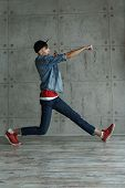 Teenage boy in jeans and red sweater, denim jacket and baseball cap dances hip-hop. Dynamics of modern dance movement. Youth fashion.