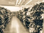 Blurred Shoes Hanging On Display At Discount Retail Store In Usa poster