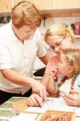stock photo of nana  - Grandma mother and grand daughter painting together  - JPG