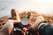 Hipster Traveler Sitting And Hold In Hand Compass. Pov View. Blurred Background. Flare Effect poster