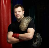 Young Man With Grungy Boxing Gloves On Shoulder. Boxing Theme poster