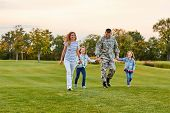 Happy Family Walking On The Grass. Soldier With His Wife And Daughters In The Park. poster