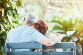 Back view of affectionate senior spouses having rest on bench in natural environment poster