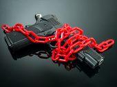 Reform Gun Control Concept. Red Chain Around Handgun On Black Mirror With Spotlight Shine To The Gun poster