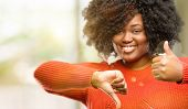 Beautiful african woman confused with thumbs up and down, trying to take a decision expressing doubt poster
