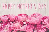 Happy Mothers Day Text On Pink Peonies Bouquet On Rustic White Wooden Background, Top View. Floral  poster