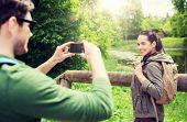 travel, hiking, backpacking, tourism and people concept - smiling couple with backpacks taking pictu poster