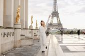 Blonde Female Person Walking On Trocadero Square Near Gilded Statues And Eiffel Tower In Paris. Conc poster