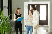 Friendly Realtor Or Landlord Talking Showing Modern Luxury House For Sale To Young Couple Customers, poster