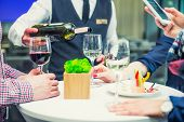 Professional Waiter In Uniform Serving Wine To Guests Of Event. Catering Or Celebration Concept. Ser poster