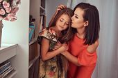 Fashion Family. Tender Mother Kissing Cute Daughter At Home. Little Girl Hugging Her Mother, Standin poster