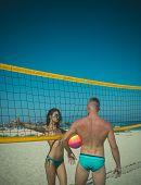 Young Sporty Active Couple Stand Near Volleyball Net, Play Game On Summer Day. Couple Have Fun Playi poster