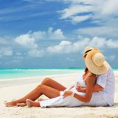 Happy honeymoon vacation at Paradise. Couple relax on the white sand of beach. Happy sea lifestyle.  poster