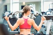 Side view of a determined and beautiful fit woman cycling on stationary bicycle during workout for b poster