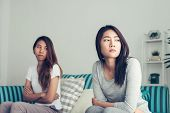 Young Asian Lesbian Couple Argue And Turn Their Back To Each Other In The Period Of Sad In The Bedro poster