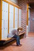 stock photo of snob  - Portrait of a lonely student sitting in a corridor - JPG