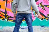 Постер, плакат: A Young Graffiti Artist In A Gray Hoodie Looks At The Wall With His Graffiti In Pink And Green Color