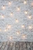 Light Bulbs On White Brick Background With Wooden Floor. Vintage Edison Light Bulbs Garland In Loft  poster