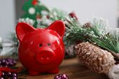 Close-up Of Bright Red Piggy-bank On Wooden Table. Pinecones And Nice Purple Beads Decorations. Spri poster