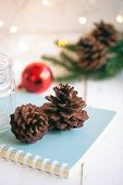 Christmas Pine Cone Or Conifer Cones On Blue Notebook Near Bottle And Red Bubble Ball On White Wood  poster
