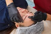 The Master Removes Excess Eyebrow Makeup Paint After The Procedure. poster