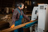 Woodworker works on machine, lumber industry poster