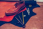 Classic Brown Shoes And Leather Shoemaking Tools And Set Of Leather Craft Tools poster