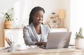 Female Entrepreneur. Smiling African American Businesswoman Working On Laptop In Modern Office, Copy poster