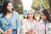 Happy Asian Girlfriends Walking In The City While Watching On Mobile Smartphones - Young Teen Girls  poster