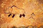 stock photo of primitive  - Cave painting of primitive man hunting for mammoth - JPG
