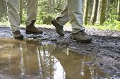 Low section of hikers walking through a mud puddle in forest