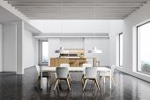 Spacious White Kitchen With Bar And Dining Table poster