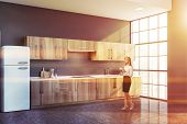 Blonde Woman Standing In Stylish Kitchen With Gray Walls, Wooden Countertops And Cupboards And White poster