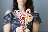The Girl Holds Colored Christmas Candies In Her Hands. Sweets In The Foreground. Christmas Concept poster