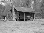 image of outhouse  - wooden cabin with rock fireplace with and outhouse in back - JPG