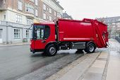 stock photo of trash truck  - Red garbage disposal truck parked at the side of a street collecting household rubbish and waste for crushing recycling and treatment or disposal on municipal dumps - JPG